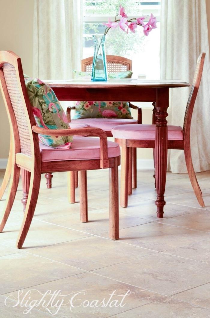 ein wohnzimmer mit stühle aus holz und mit pinken kissen, ein tisch mit einer kleinen blauen vase mit pinken blumen, zwei weiße vorhänge und ein fenster und kissen mit flamingos