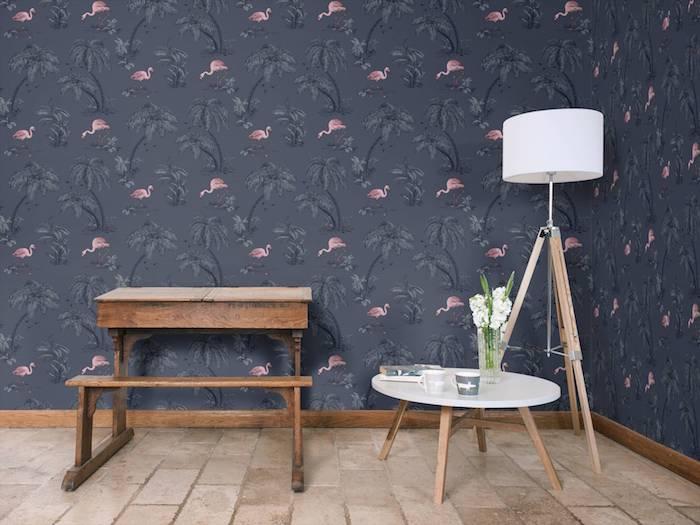 eine wand mit einer großen schwarzen flamingo tapete und ein kleiner tisch aus holz, eine weiße lamoe und ein weißer tisch mit einer vase mit weißen blumen