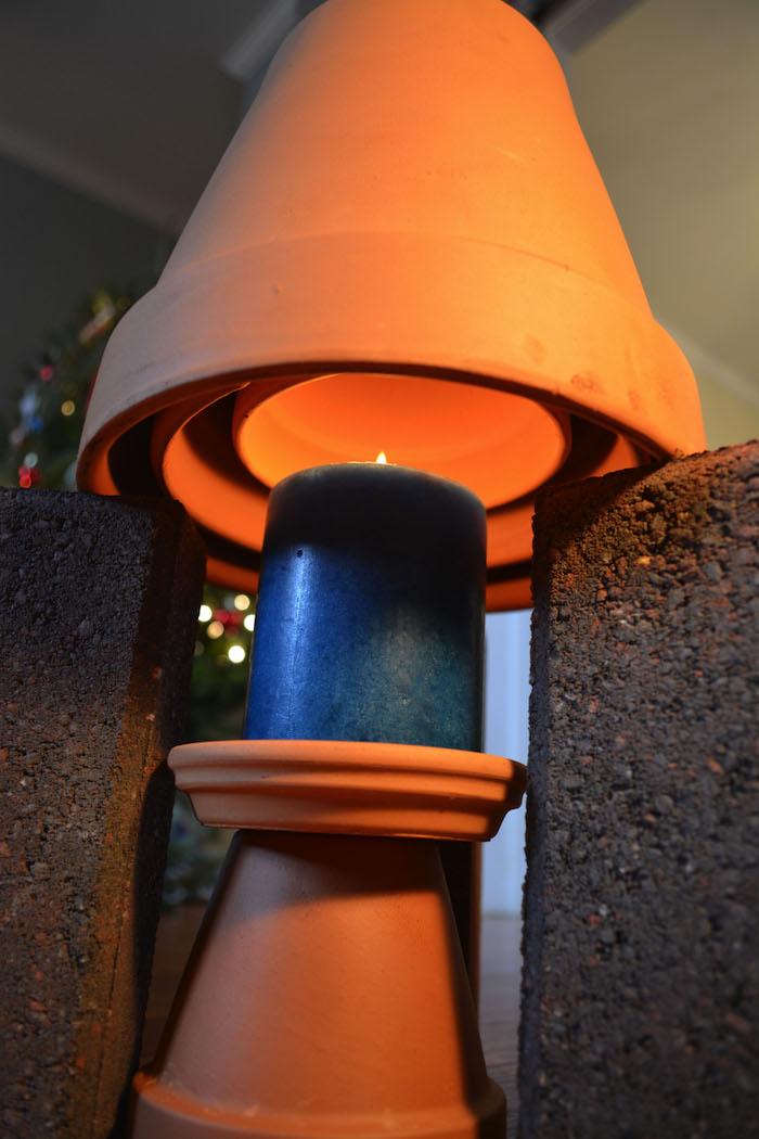 eine blaue kerze und zwei braune ziegel und ein ein teelichtofen mit einem großen braunen blumentopf aus keramik, diy teelichtofen