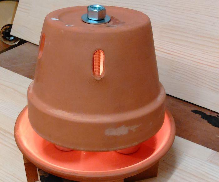 ein tisch aus holz, ein teelichtofen mit einem großen braunen blumentopf, einer schraube und einem bolzen aus metall, teelichtofen bauen