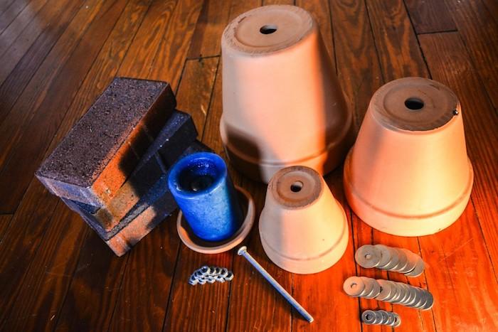 ein boden aus holz, drei große ziegel und drei braune blumentöpfe aus keramik, eine blaue kerze, schrauben und bolzen aus metall, teelichtofen materialliste