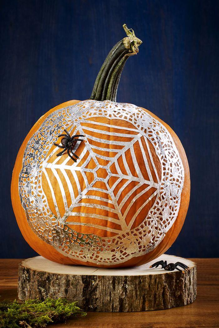 zwei kleine schwarzen spinnen und ein graues spinnennetz, halloween deko, oranger großer kürbis halloween und eine blaue wand