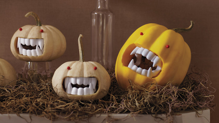 drei graue und gelbe gruselige halloween kürbisse mit kleinen roten augen und mit scharfen großen und weißen zähnen, colle kürbisgesichter, halloween deko selber basteln