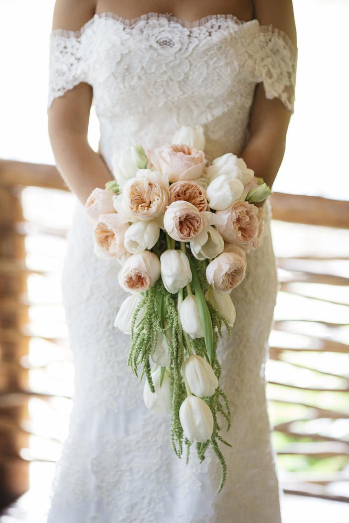 eine terrasse und eine junge braut mit einem weißen vintage brautkleid und einem vintage brautstrauß wasserfall mit pinken und weißen rosen und tulpen und grünen blättern