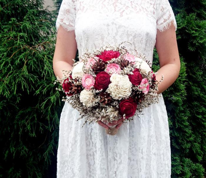 ein garten mit grünen pflanzen und braun mit einem weißen brautkleid, ein strauß mit vielen roten, pinken und weißen rosen und kleinen braunen tannenzapfen, basteln mit tannenzapfen