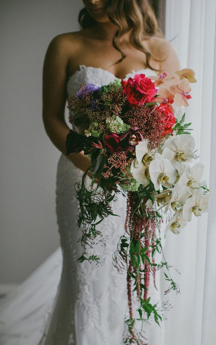 ein fenster mit einem weißen vorhang und eine braut mit einem weißen kleid und einem langen großen brautstrauß mit vielen grünen blättern und roten rosen und weißen blumen