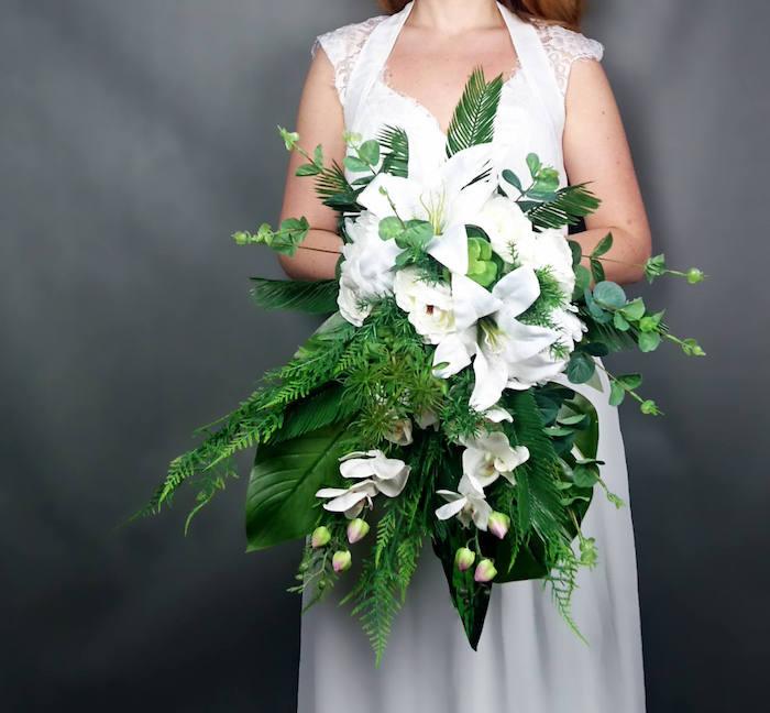 eine schwarze wand und eine braut mit einem weißen brautkleid und mit einem brautstrauß weiß mit weißen rosen und grünen blättern, ein brautstrauß hortensie