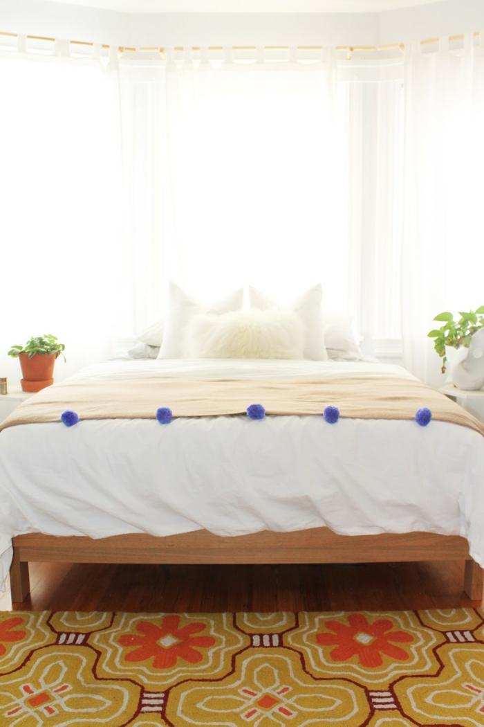 ein Bett mit bunter Decke, Verzierung aus blauen Pompons, Pompons selber machen