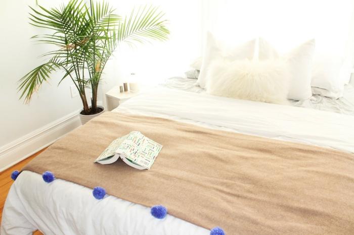 blaue Pompons selber machen und auf Decke nähen, braune Decke mit Buch darauf