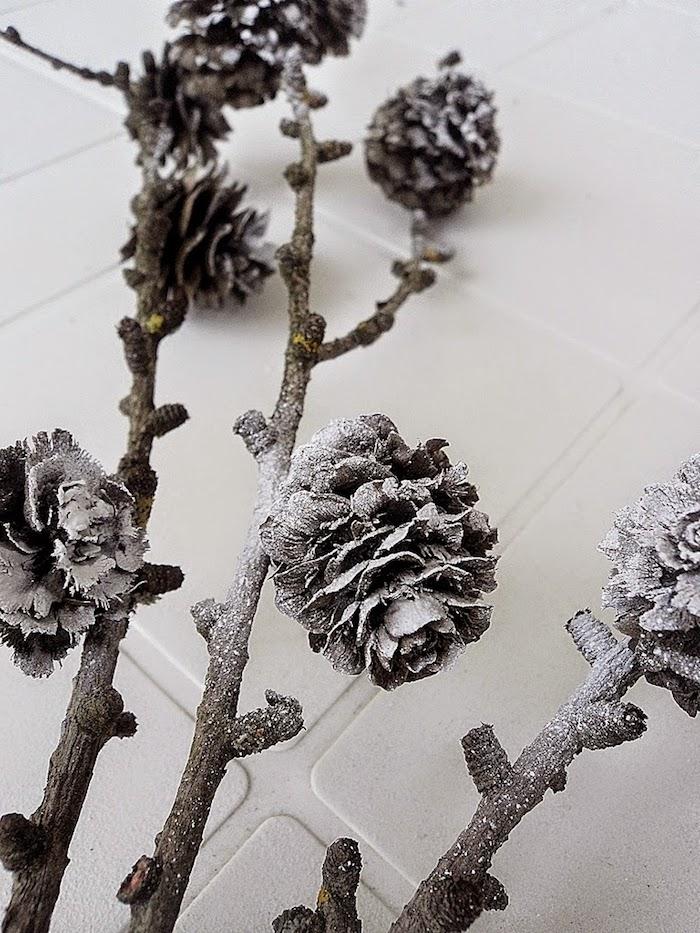 ein boden aus weißen fliesenund äste mit vielen kleine grauen bemalten tannenzapfen, eine tannenzapfen deko selber basteln