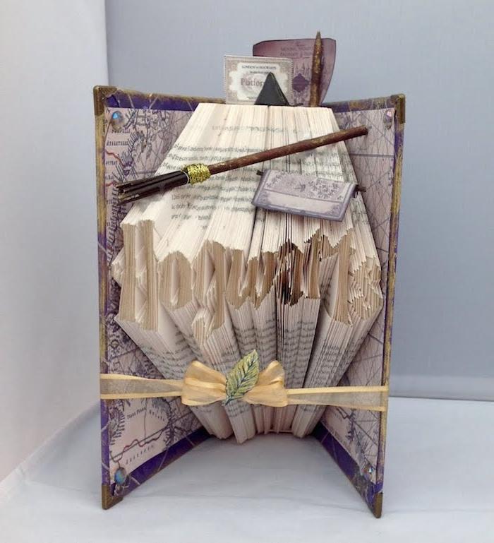 ein braner zauberstab aus holz und ein hogwarts kleines gefaltetes buch mit motiven von den harry potter romanen und mit einem violetten bucheinband