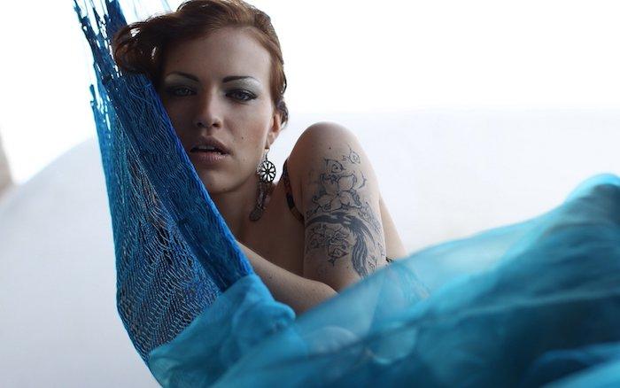 eine jnge frau mit einem tattoo arm frau, ein tattoo mit weißen und schwarzen exotischen blumen, eine frau und eine große blaue hängematte