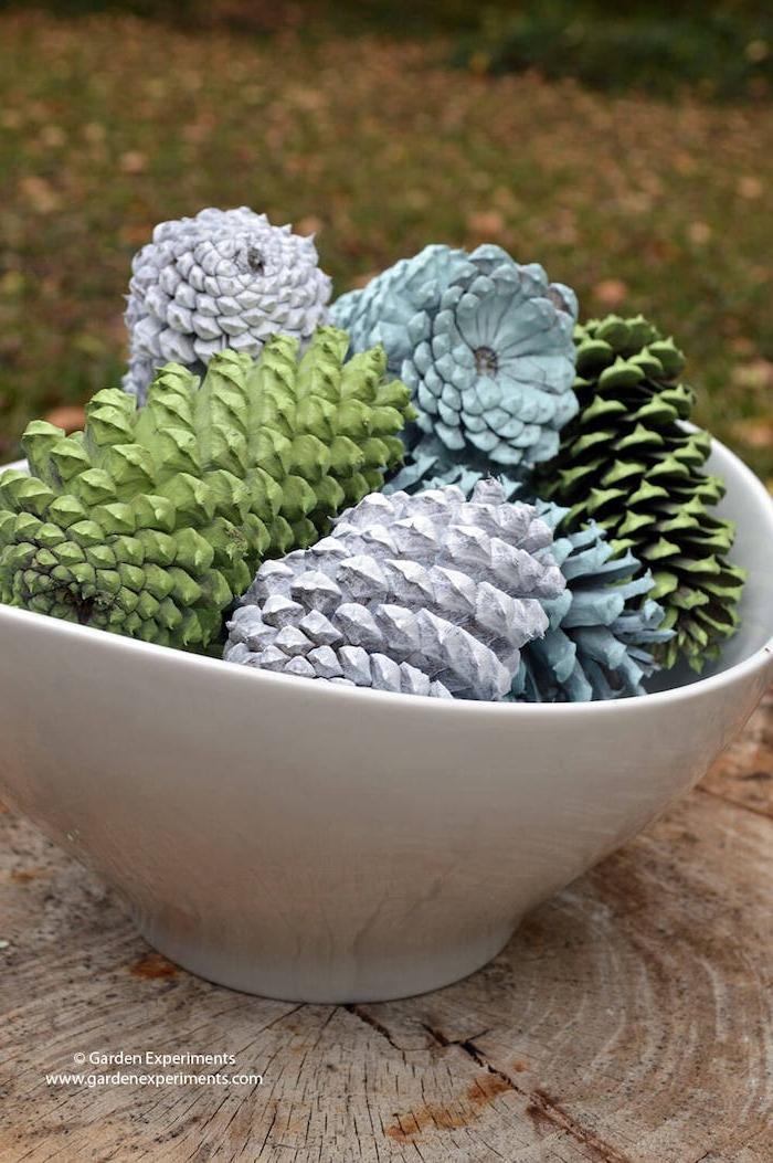 ein tisch aus holz, tannenzapfen bemalen, eine große weiße schüssel mit vielen großen bemalten grünen und weißen und blauen tannenzapfen