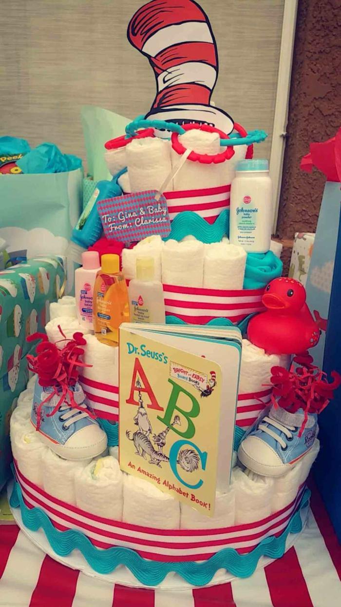 eine Windeltorte mit verschiedenen Babysachen, kleine Schuhchen und Spielzeuge