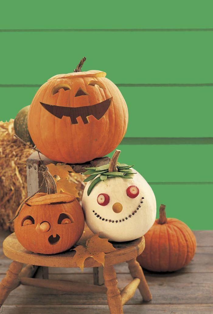 eine grüne wand und ein brauner tisch aus holz, halloween tisch dekoration mit kleinen weißen und orangen halloween kürbissen, einen kürbis schnitzen, lustige kürbisgesichter schnitzen