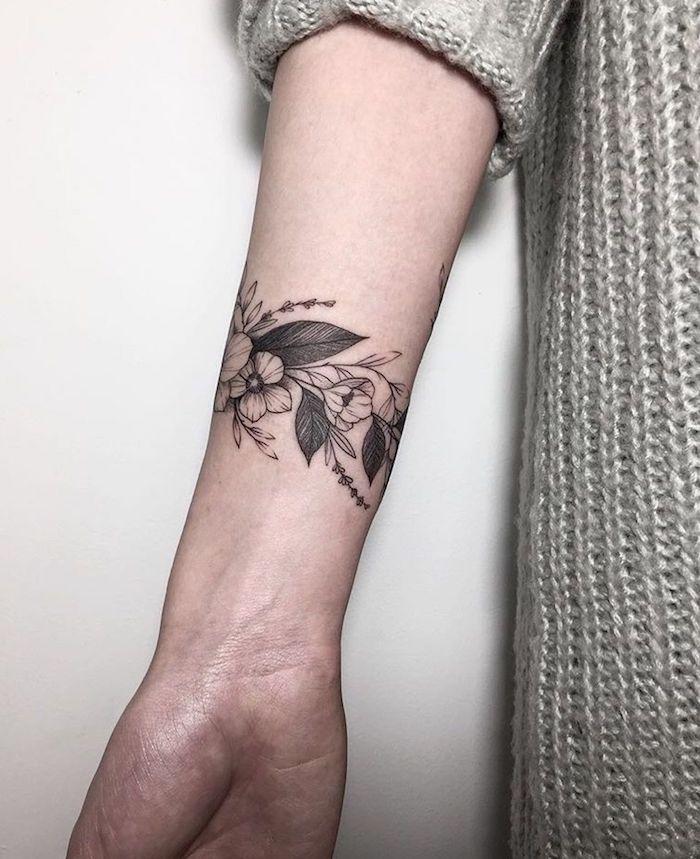 weiße wand und eine junge frau mit einer hand mit einem schwarzen tattoo mit kleinen weißen und schwarzen blumen und schwarzen blättern, frauen tattoos ideen, arm tattoo frau
