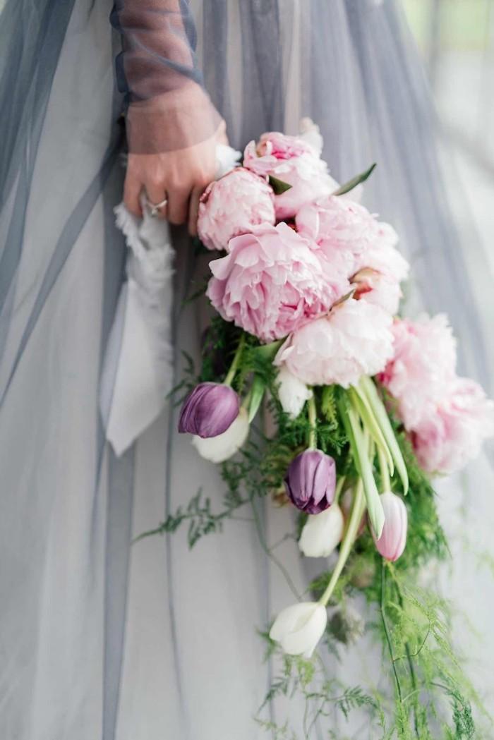 eine hand mit einem ring und eine junge braut mit einem violetten brautkleid und einem großen brautstrauß mit pinken rosen und violetten und weißen tulpen und vielen grünen blättern