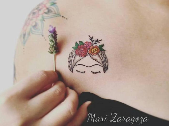 eine hand mit einer kleinen violetten blume, eine fra mitr einem kleine tattoo mit einer frau mit schwarzen augen und nblumen und grünen blättern