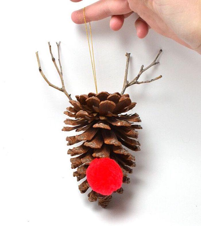 eine hand mit einem kleinen dekorativen diy hirsch aus einem tannenzapfen, ein hirsch mit einer roten nase und mit hörnern aus kleinen ästen, basteln mit tannenzapfen weihnachten