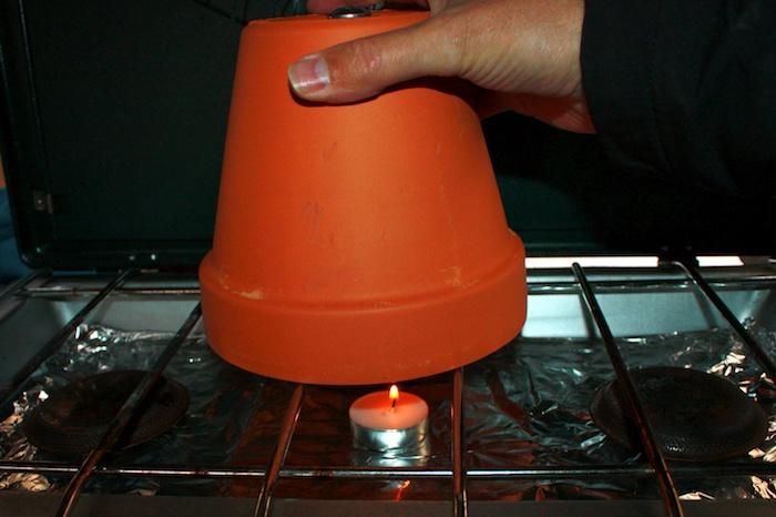 eine hand und ein brauner blumentopf aus keramik und eine kleine weiße teelicht, einen teelichtofen selber machen