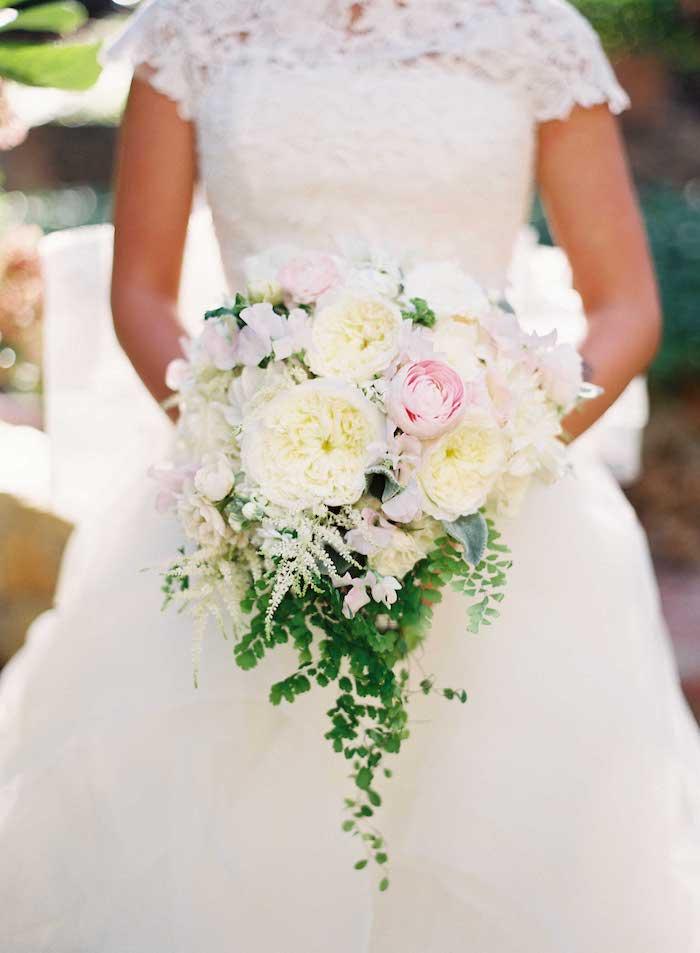 junge frau mit einem großen weißen brautstrauß mit vielen weißen und pinken rosen und kleinen grünen blättern,eine frau mit einem brautkleid