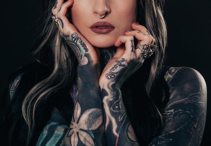 eine junge frau mit roten lippen und pearcing und zwei hände mit tattoos unterarm mit schriftarten und mit großen weißen blumen