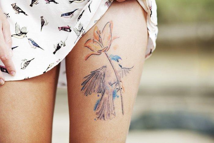tattoos frauen, eine frau mit einem weißen kleid mit vielen kleinen schwarzen fliegenden vögeln und mit einem tattoo mit einer rose und einem blauen vogel, frauen tattoo