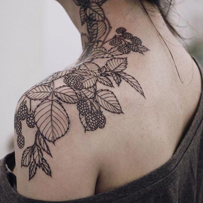 tattoo mit vielen großen schwarzen früchten und schwarzen blättern, eine junge frau mit einem arm tattoo