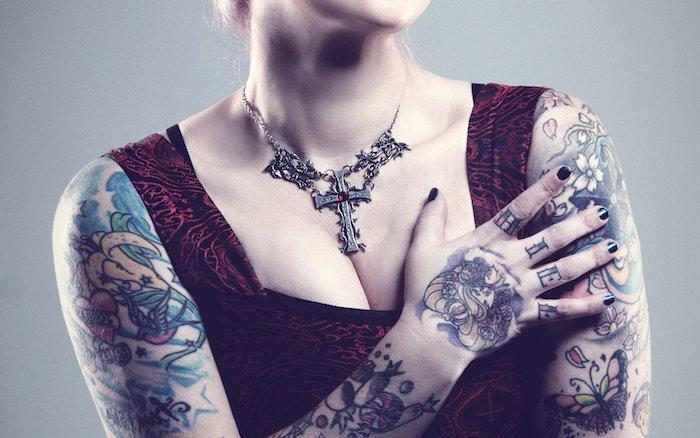 eine halskette aus metall und mit einem kreuz, eine junge frau mit händen mit arm tattoos mit sch,metterlingen und mit weißen blumen und roten herzen
