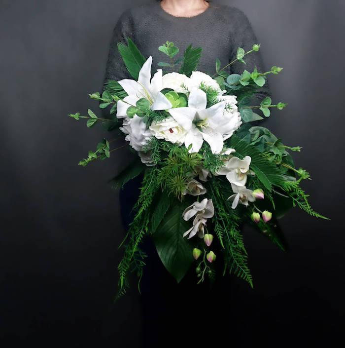 eine schwarze wand und eine frau mit einem schwarzen kleid und ein großer brautstrauß mit vielen weißen rosen udn blumen und grünen langen blättern, einen wasserfall brautstrauß gestalten