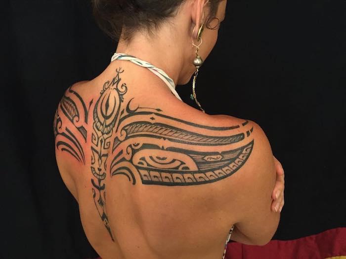 eine junge frau mit einer kette und mit einem tattoo rücken mit vielen schwarzen maori motiveb, augen und fischen, tattoos frauen