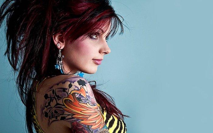 eine blaue wand und eine frau und eine rote haare und eine hand mit einem farbigen arm tattoo mit einem orangen flügel und orangen federn und sternen