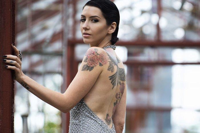 eine schwarze haare und eine junge frau mit einem schwarzen phönix tattoo rücken und eine hand mit zwei roten rosen mit grünen blättern, tattoos frauen