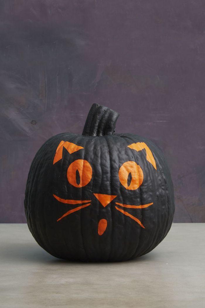 eine violette wand und eine schwarze katze aus einem großen kürbis, eine katze mit großen orangen augen und ohren, lustige kürbisgesichter malen