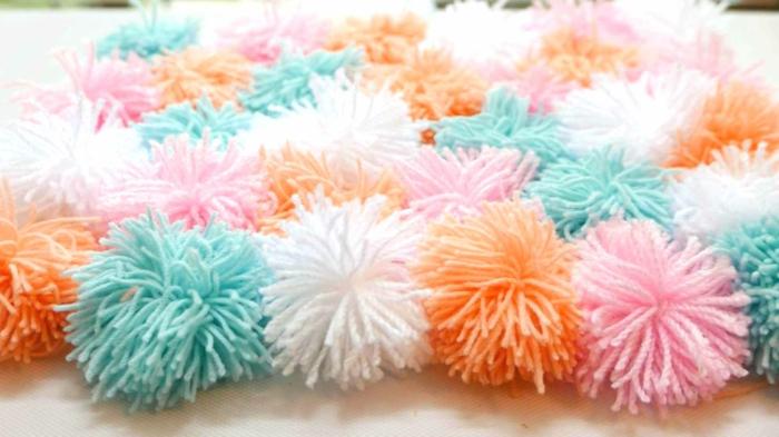 bunte Bommel in blauer, rosa, weißer und oranger Farbe wie Teppich, Pompons selber machen