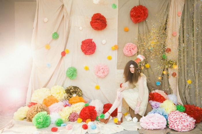 ein kunstvolles Foto von einem Mädchen und viele Pompons, Pompons selber machen