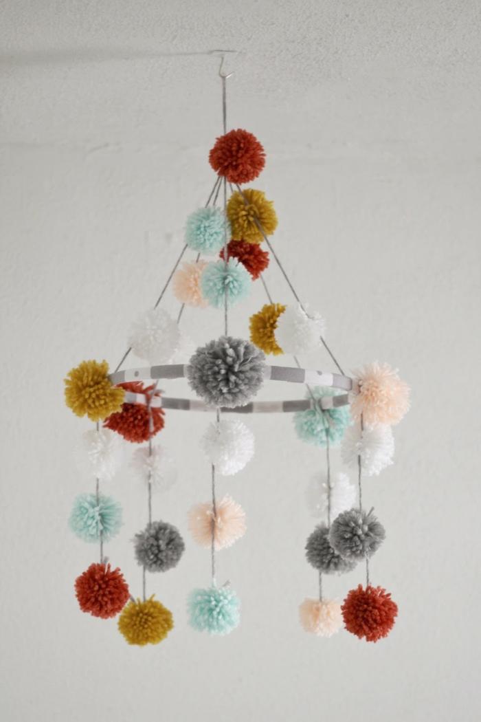 eine Mobile mit Pompons in verschiedenen Farben, Basteln mit Wolle, so entzückend