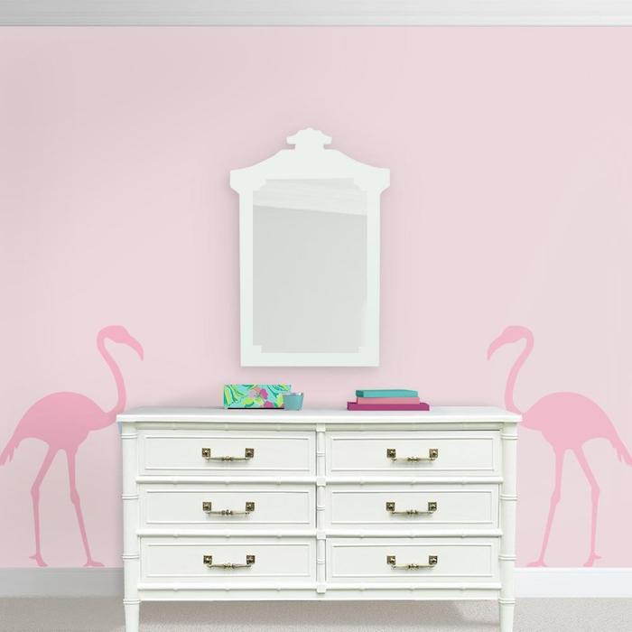 eine pine flamingo tapete und ein weißer spiegel, eine pinke wand mit zwei großen pinken flamingos mit pinken federn
