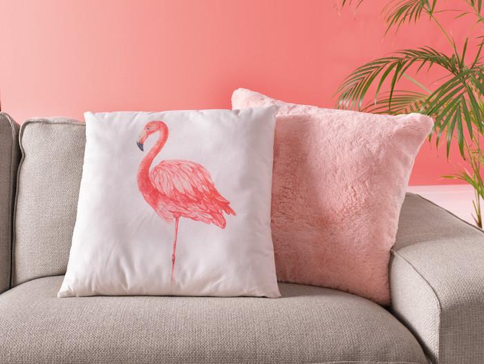 eingraues sofa mit einem pinken kissen und einem kleinen weißen kissen mit einer pinken flamingo mit pinken federn, flamingo deko