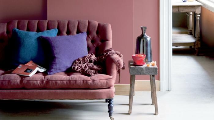 ein rosa Sofa, blaue Kissen, kleiner grauer Tisch, Altrosa Wandfarbe, ein weißer Boden