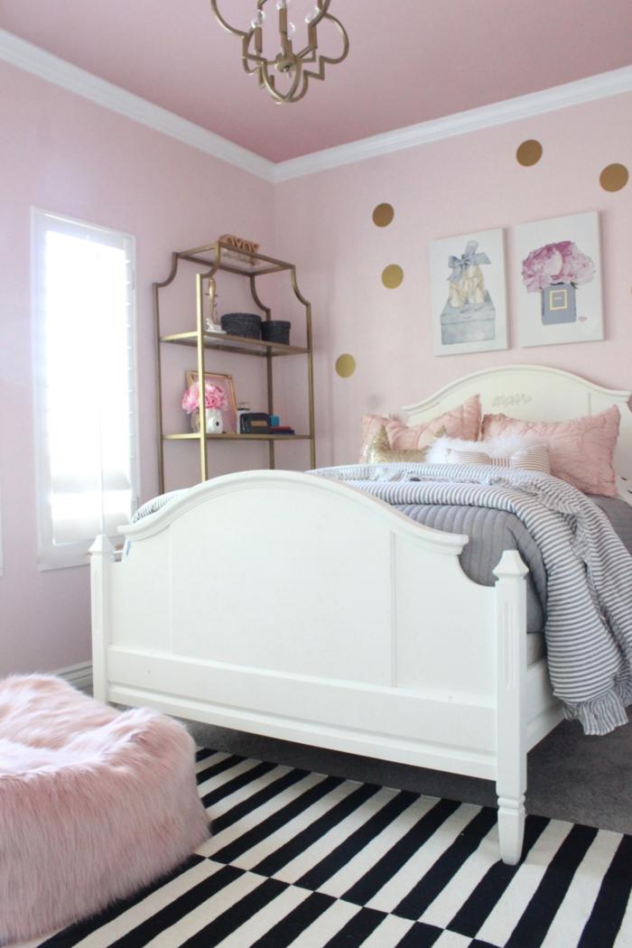 Altrosa Wandfarbe, ein großes Bett, gestreifter Teppich, ein Regal in goldener Farbe