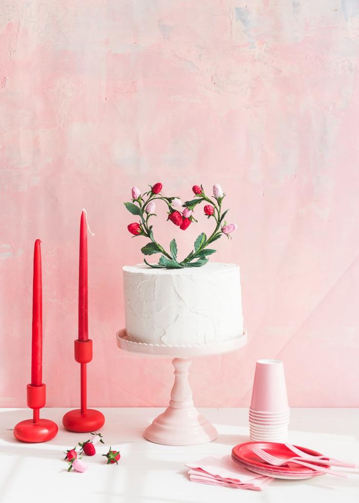 eine weiße Torte mit Blumen als Dekoration, zwei Kerzen und Einweggeschirr
