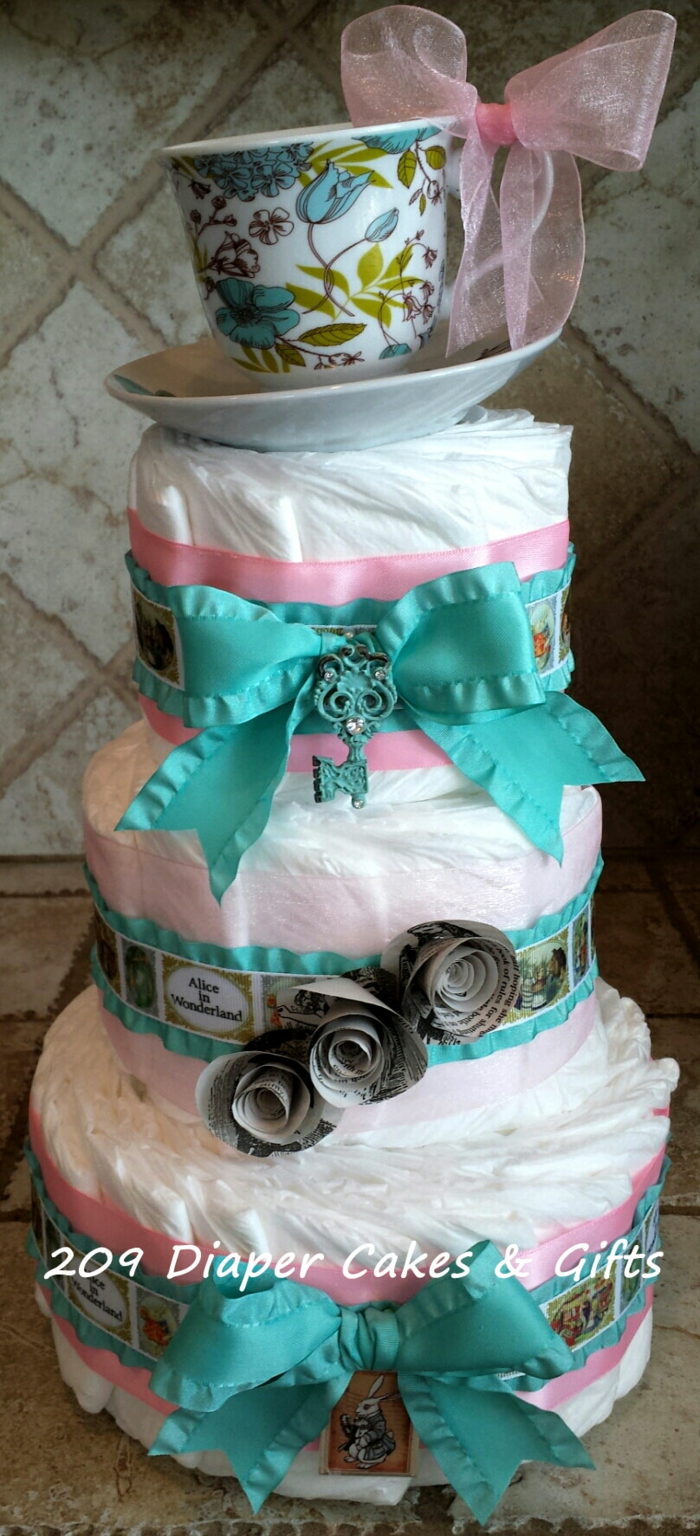 Windeltorte mit rosa und blauer Farbe, ein Porzellantasse an der Spitze, kleine Papierrosen