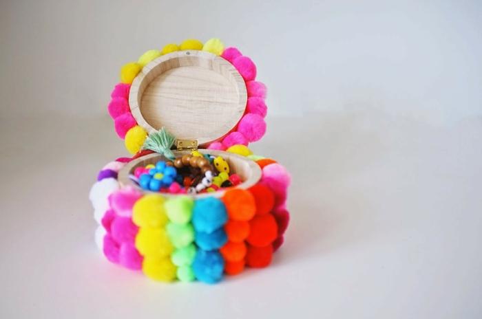 bunte Bommel als Dekoration von einem runden Schmuckbox, Basteln mit Wolle