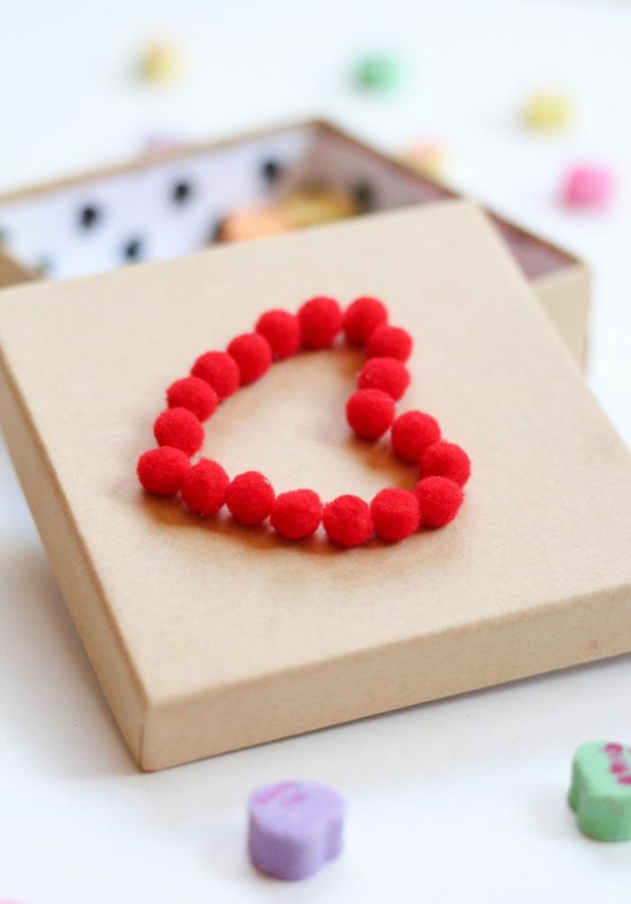 eine Schachtel mit roten Pompons in der Form von Herz auf einer Schachtel, kleine Bonbons, Basteln mit Wolle
