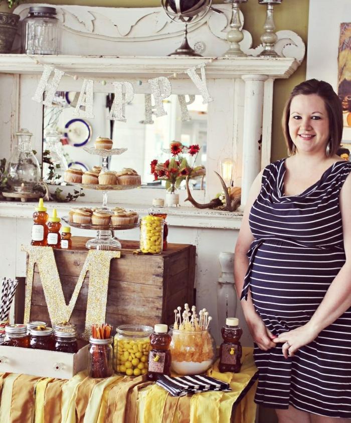 die Mutter steht stolz auf die Dekoration am Tisch, Babyparty Ideen für Motto-Party