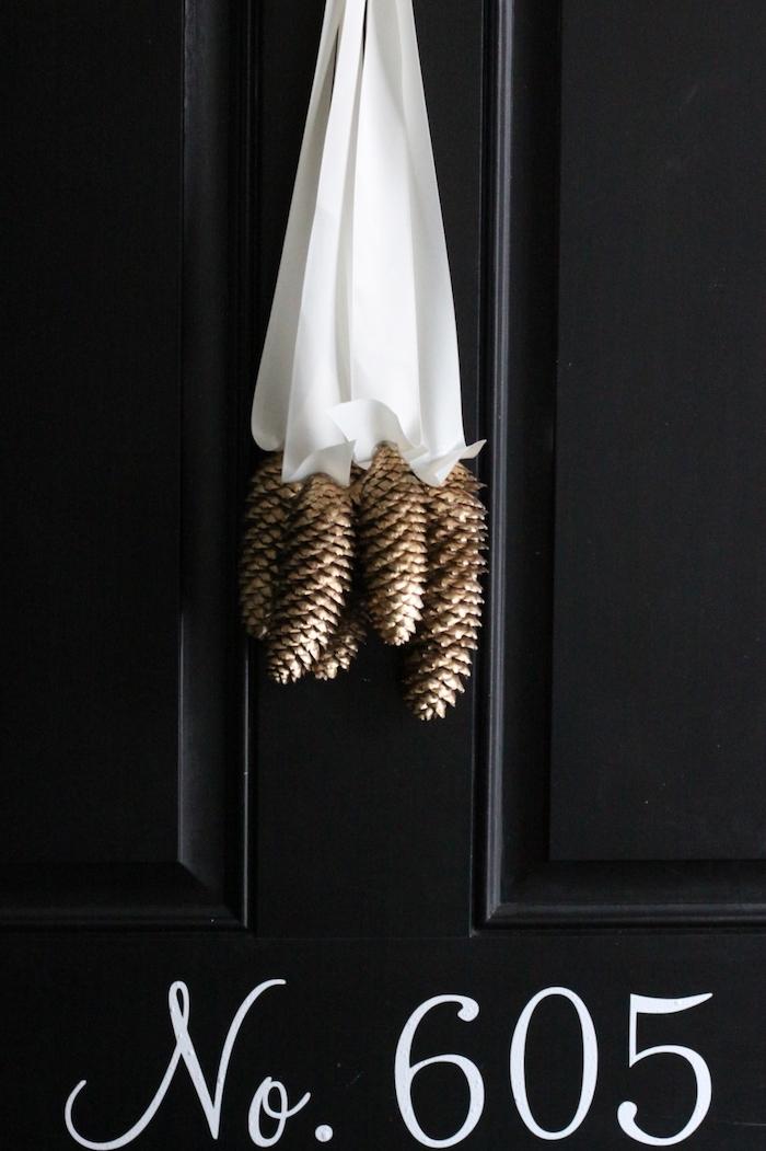 ein schwarzer tisch aus holz und eine deko mit einer weißen schleife und mit vielen bemalten goldenen tannenzapfen, eine deko mit tannenzapfen selber basteln