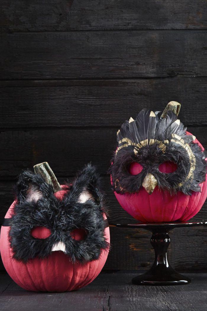eine wand mit schwarzen holzbrettern, zwei violette kürbisse mit zwei schwarzen masken mit schwarzen federn, halloween dekoration selber basteln