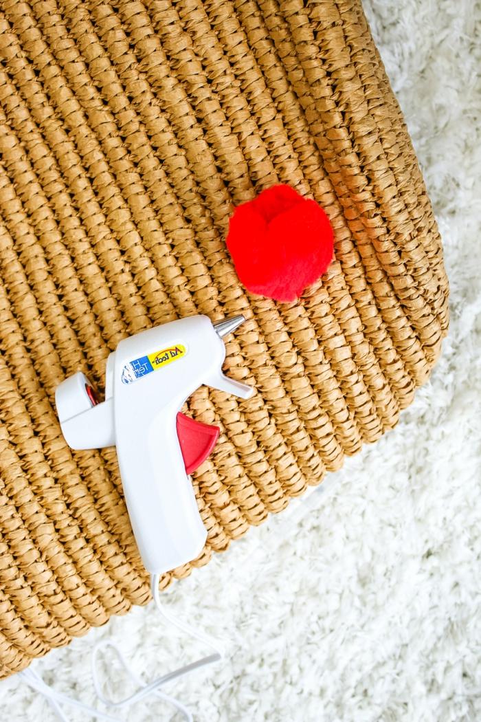 ein roter Pompon, Tasche und Heißkleber, wie die Pompons zu der Tasche zu fixieren