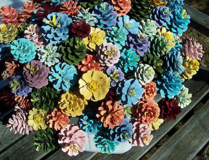 ein tisch aus holz und eine vase mit einem bunten deko strauß aus vielen gelben, grünen, roten, blauen und violetten blumen aus bemalten tannenzapfen, eine frühlingsdeko selber machen, tannenzapfen bemalen ideen